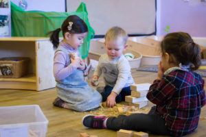 nursery students sitting on the floor playing